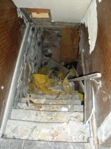 Stairway leading to the basement, which is blocked by debris